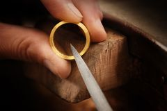 Goldsmith hand holds a golden ring and works on it with a metal. File, close up with copy space,  focus, narrow depth of field Stock Photo