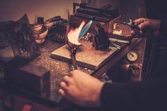 Goldsmith melting gold to liquid state. Royalty Free Stock Photo