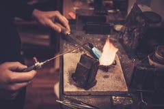 Goldsmith melting gold to liquid state. Royalty Free Stock Image