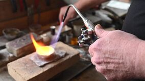 Goldsmith melts gold in a liquid state in a crucible. Craft jewelery 4k quality