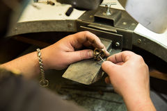 Goldsmith. Polishing gold ring with hands royalty free stock photography