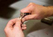 Goldsmith. Polishing gold ring with hands stock photos
