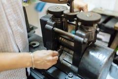 Goldsmith using machine. To make metal thinner Stock Photos