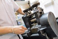 Goldsmith using machine. To make metal thinner Stock Photography