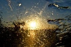 Goldsonnenuntergang-Zusammenfassungsregen auf der vorderen Windschutzscheibe des Autos Stockbild