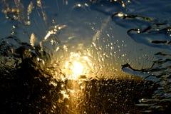 Goldsonnenuntergang-Zusammenfassungsregen auf der vorderen Windschutzscheibe des Autos Stockfotografie