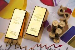 Goldstäbe und -münzen auf Diagrammen! Stockbilder