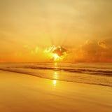 Goldstrand und Seesonnenuntergang Stockfotos