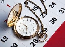 Goldtaschenuhr und ein Wandkalender Stockfotografie