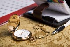Goldtaschenuhr und ein Wandkalender und ein Sketchpad Stockbild
