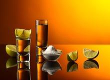 Goldtequila auf einem schwarzen reflektierenden Hintergrund Lizenzfreie Stockbilder