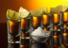 Goldtequila auf einem schwarzen reflektierenden Hintergrund Lizenzfreies Stockbild