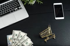 Goldwarenkorb, -bargeld und -geräte auf einer schwarzen Tabelle Lizenzfreie Stockfotos