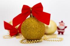 Goldweihnachtsbälle mit rotem Band, Perlen und Sankt auf weißem Hintergrund Stockfoto