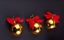 Goldweihnachtsbälle mit roten Bändern Stockfotografie