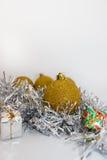Goldweihnachtsbälle und -geschenke auf glänzendem silbernem Band auf weißem Hintergrund Stockfoto