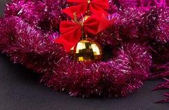 Goldweihnachtsbälle und helles funkelndes goldenes Lametta mit roten Bögen Lizenzfreie Stockfotografie