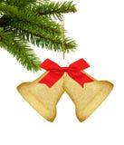 Goldweihnachtsdekorglocken mit rotem Bogen auf grünem Baum lokalisierten O Stockfotos