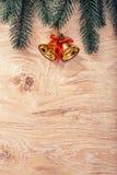 Goldweihnachtsglocken und Tannenbaumast auf einem rustikalen hölzernen Hintergrund Abbildung innen Glückliches neues Jahr Beschne Stockfotografie