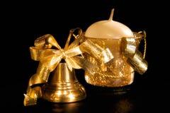 Goldweihnachtshandbell und -kerze lizenzfreie stockbilder