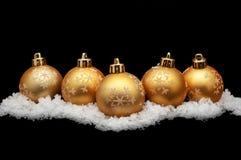 Goldweihnachtskugeln mit Schnee Stockbild