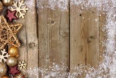 Goldweihnachtsverzierungs-Seitengrenze mit Schneerahmen auf Holz stockfotografie