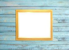 Goldweinlese-Bilderrahmen auf blauem hölzernem Hintergrund Lizenzfreie Stockfotos