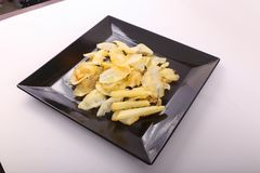 French fries. Goldy Potato Chips on black plate Stock Photography