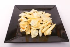 French fries on black dish. Goldy Potato Chips on black plate Royalty Free Stock Image