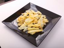 French fries on black dish. Goldy Potato Chips on black plate Stock Images