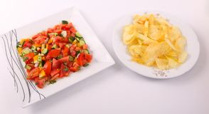 Potato Chips with salad as a meal. Goldy Potato Chips on white plate with mixed vegetables salad on modern white dish Stock Images