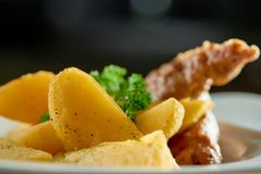 Goldy potatoes slices with sausages and parsley. Close-up of goldy fried potatoes slices with roasted sausage and parsley on whe white plate Stock Photos