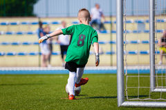 Goleiros novo do futebol do futebol do menino que retrocede a bola de futebol em um sp Imagem de Stock