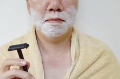 golenie śmietanka na mężczyzna twarzy z wiórkarką na prawej ręce przygotowywa ogolony Zdjęcia Royalty Free