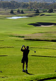 Golf. A golfer tees off in silhouette Stock Images