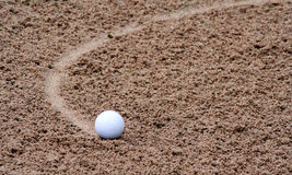 Golf. Ball rolling in to bunker Stock Images