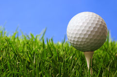 Golf. Golf ball on tee against blue sky Stock Photo