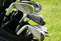 Golf. Clubs in bag, green grass background Stock Images