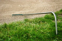 Golf. Rake in sand bunker in golf course Stock Photography