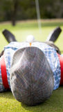 Golf. Er Relaxes Laying Down On A  Green Near The Ninth Hole With A  Tee And  Ball In His Mouth In A Sporting Concept With Copyspace On His Flat Cap Stock Photos