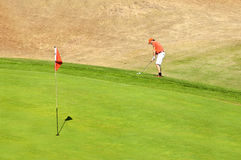 Golf. Player using a wedge to put his ball on the green near the hole Stock Photos
