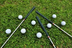 Golf. Balls on tees with the clubs laying on the green grass stock photography