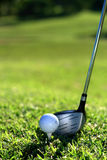 Golf. A golf club (driver) about to strike a golf ball on a tee Stock Image