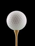 Golf. Ball on a tee, isolated on black Royalty Free Stock Photography
