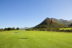 Golf #55. A golf course by the mountains. Red flag on the green Royalty Free Stock Photos