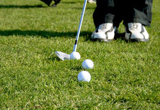 Golf. A golf club (driver) about to strike a golf ball on a tee Royalty Free Stock Photography