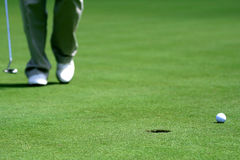 Golf. Man approaching a putt on a golf green with the ball and hole in the foreground Royalty Free Stock Image