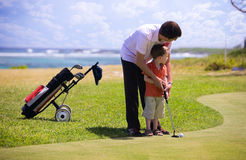 Golf. Father teaching his son how to play golf Stock Photo