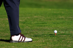 Golf. Ball and men's foot on the grass Stock Photos