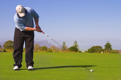 Golf. Er putting on the green.  ball in motion. Copy space Royalty Free Stock Photo